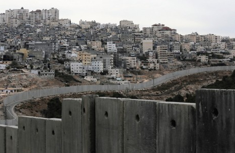 The security barrier runs along the Shuafat refugee camp. (photo credit: REUTERS)