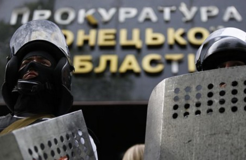 Pro-Russia activists wearing riot police helmets and shields stand guard at the entrance of the prosecutor's office in Donetsk May 1, 2014 (photo credit: REUTERS)