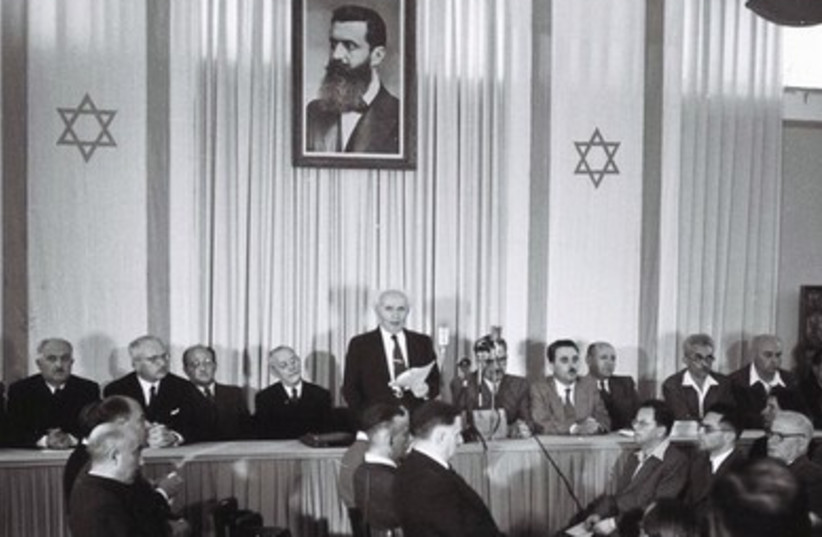 ISRAEL'S FIRST prime minister David Ben-Gurion (center) stands under a portrait depicting Theodore Herzl, the father of modern Zionism, as he reads Israel's Declaration of Independence in Tel Aviv May 14, 1948.  (photo credit: REUTERS)