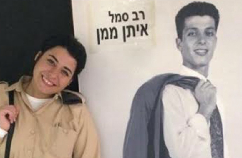 Eden Maman, head of human resources at Tel Nof Air Base, stands next to a life-size picture of her father, who was killed in a helicopter crash in Lebanon. (photo credit: IDF SPOKESMAN'S OFFICE)