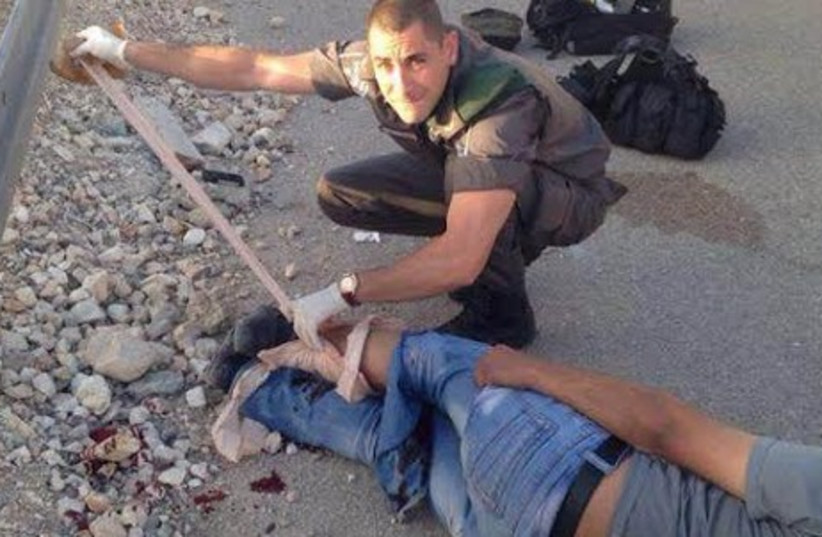 A Border Police medic treats an injured Palestinian would-be infiltrator. (photo credit: COURTESY ISRAEL POLICE)
