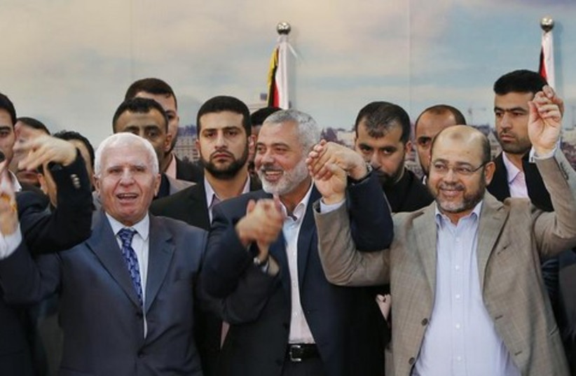 Senior Fatah official Azzam Al-Ahmed (L), head of the Hamas government Ismail Haniyeh (C) and senior Hamas leader Moussa Abu Marzouq hold their hands after announcing a reconciliation agreement in Gaza City April 23, 2014.  (photo credit: REUTERS)