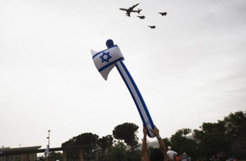 Israelis look on as a formation of IAF aircraft flies over the Knesset in Jerusalem on Tuesday. (photo credit: REUTERS)