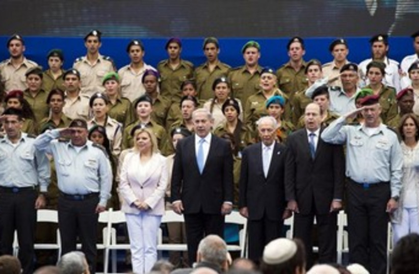 Israeli Prime Minister Benjamin Netanyahu (front row, 4th L), his wife Sara (3rd L), Israeli President Shimon Peres (4th R), Defence Minister Moshe Yaalon (3rd R), Army chief Benny Gantz (2nd R), and Gantz's wife Revital Gantz (R) sing the national anthem at an event to commemorate outstanding soldi (photo credit: REUTERS)