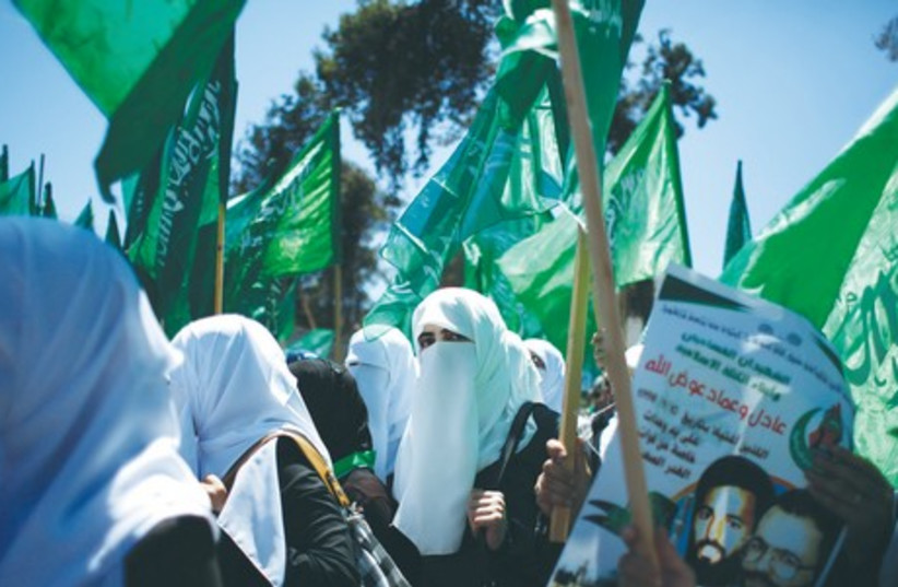 Women hold Hamas flags as they take part in the funeral of leading Hamas terrorists Imad and Adel Awadallah last month. (photo credit: REUTERS)
