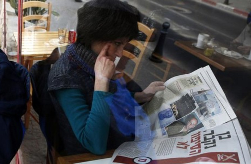 A woman is seen through a coffee shop window as she reads an article about Ben Zygier in an Yedioth Ahronoth newspaper in Jerusalem, February 15, 2013. (photo credit: REUTERS)