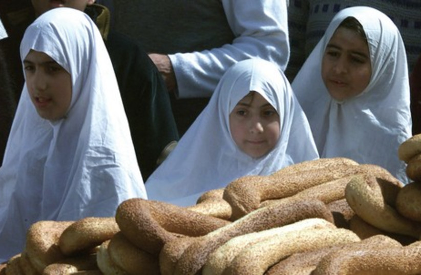 Palestinian girls pass a bread vendor in the Old City. Most Jerusalem street vendors do not have a license. (photo credit: REUTERS)