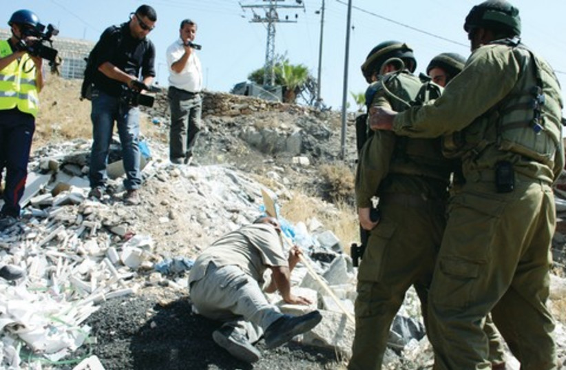 Confrontation between Israeli soldiers and a Palestinian protester in Beit Umar (photo credit: REUTERS)