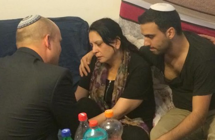 Economy Minister Naftali Bennett consoles members of the Dadon family in Afula. (photo credit: Courtesy)