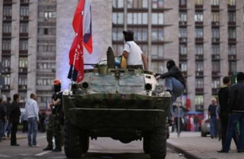 A pro-Russia rebel sits on top of an armored vehicle outside a regional government building in Donetsk, eastern Ukraine May 10, 2014. (photo credit: REUTERS)