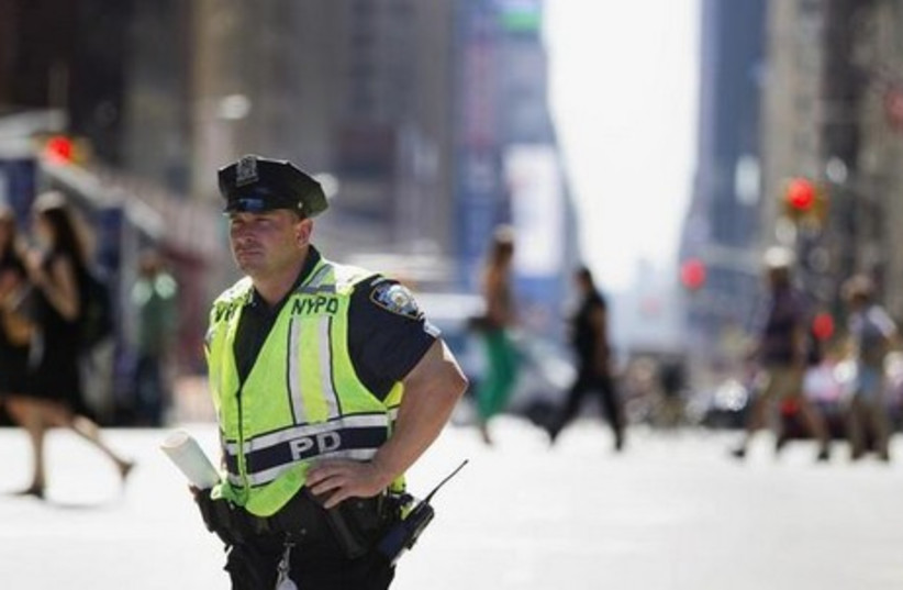 A New York Police Department officer stands in the street.  (photo credit: REUTERS)