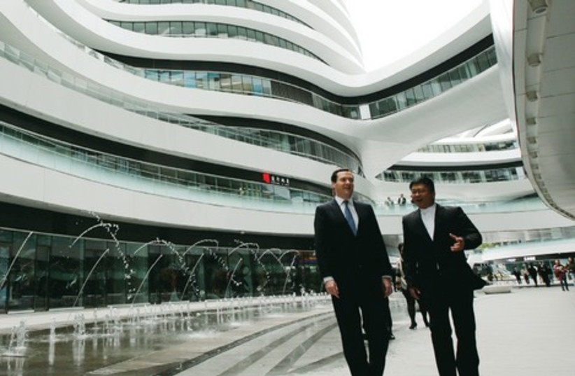 SATOSHI OHASHI (R), associate director of the Beijing Studio of Zaha Hadid Architects, accompanies Britain's Chancellor of the Exchequer George Osborne during their tour of Galaxy SOHO, a newly-built urban complex building, in Beijing last year. (photo credit: REUTERS)
