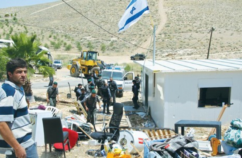 CHONI KANIEL (left) stands beside his belongings as security forces get ready to bulldoze his home in the Ma'aleh Rehavam outpost, in the Gush Etzion region of the West Bank, yesterday. (photo credit: TOVAH LAZAROFF)