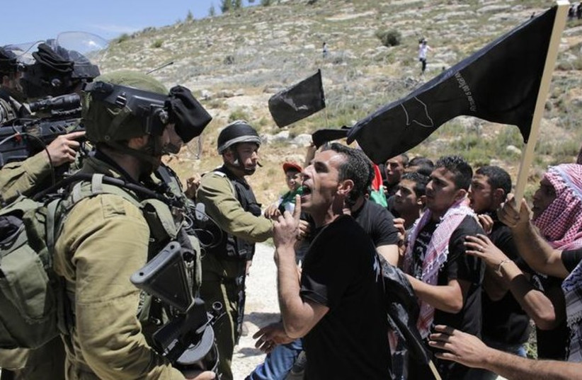 A Palestinian protester argues with IDF soldiers during a protest marking Nakba Day, May 15, 2014. (photo credit: REUTERS)
