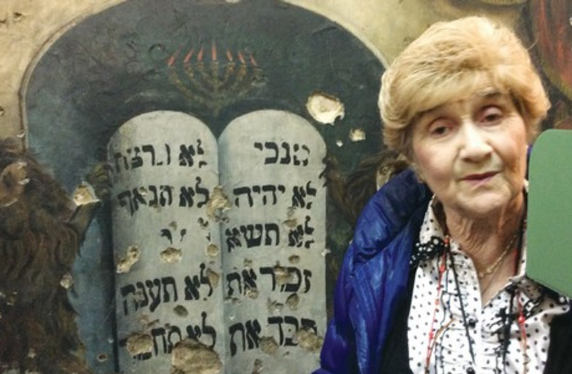 Rena Quint points out bullet holes on the wall of what once was the Piotrkow Central Synagogue and now serves as a library. ( (photo credit: Courtesy)