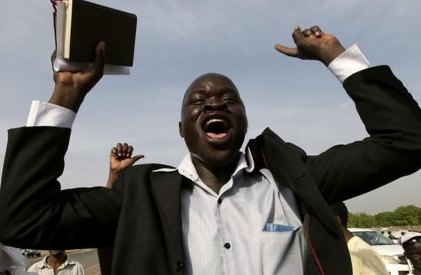 A Christian holds up a bible as he chants slogans during a parade in support of the referendum on south Sudan independence in Juba. (photo credit: REUTERS)