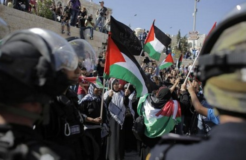 Palestinian protesters wave flags as Israeli policemen guard nearby during a demonstration marking Nakba Day. (photo credit: REUTERS)