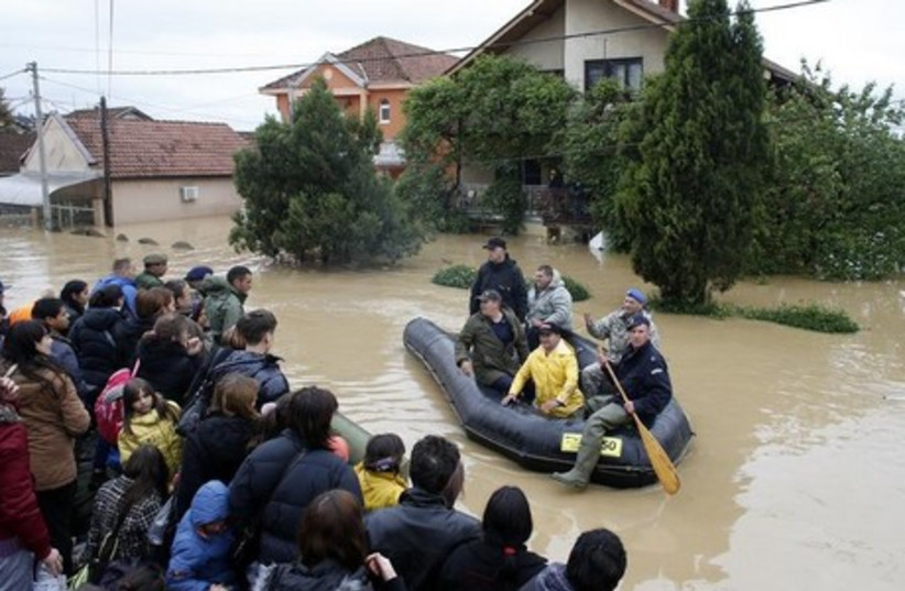 Serbian army soldiers evacuate people in the flooded town of Obrenovac, southwest of Belgrade, Serbia May 17, 2014. (photo credit: REUTERS)