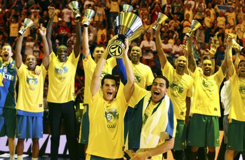 Maccabi Tel Aviv's Guy Pnini (L) and David Blu hold the trophy as they celebrate with teammates after winning their Euroleague Final Four final basketball game against Real Madrid, in Milan May 18, 2014. (photo credit: REUTERS)