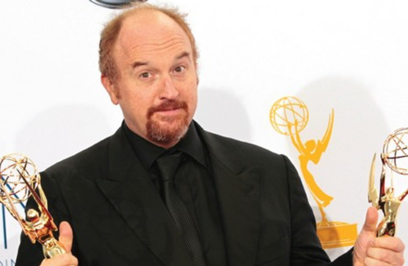 LOUIS CK holds Emmy awards for his show 'Louie' at the 64th Primetime Emmy Awards in Los Angeles in 2012. (photo credit: REUTERS)