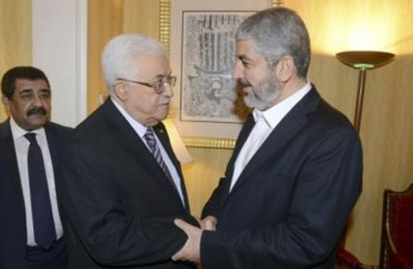 Palestinian President Mahmoud Abbas (L) shakes hands with Hamas chief Khaled Mashaal in Doha May 5, 2014. (photo credit: REUTERS)