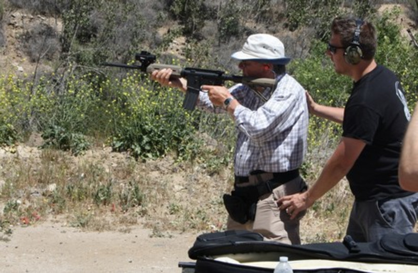 Itamar Gelbman adjusts survivor Les Hajnal's stance as he fires an AR15 rifle, during a shooting class for American Children of Jewish Holocaust Survivors. (photo credit: ANTHONY WEISS)