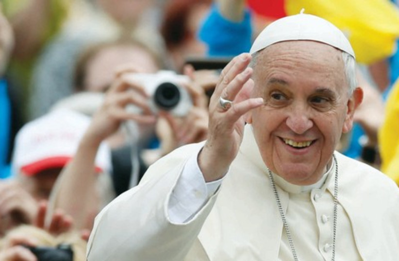Pope Francis greets the faithful as he rides in his Popemobile (photo credit: REUTERS)