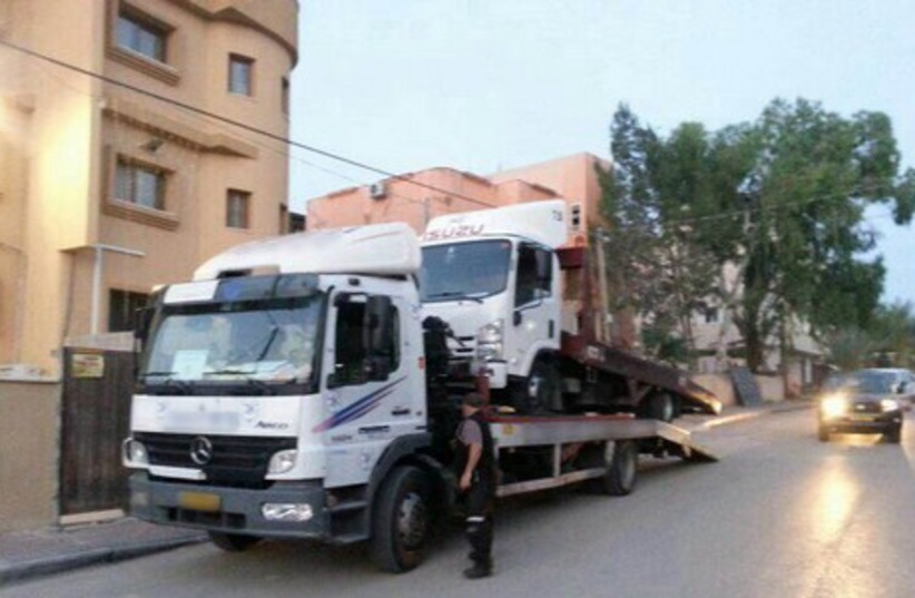 Towing one of the illegal trucks. (photo credit: ISRAEL POLICE)