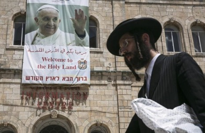 An ultra-Orthodox Jewish man walks past a banner depicting Pope Francis, in Jerusalem's Old City (photo credit: REUTERS)