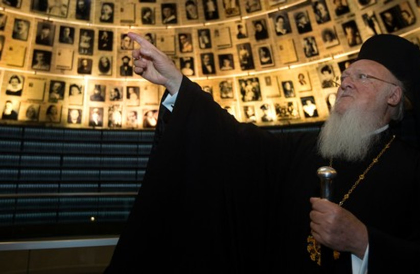 Ecumenical Orthodox Patriarch Bartholomew I of Constantinople looks at pictures of Jews killed in the Holocaust during a visit to Yad Vashem, May 27, 2014. (photo credit: REUTERS)