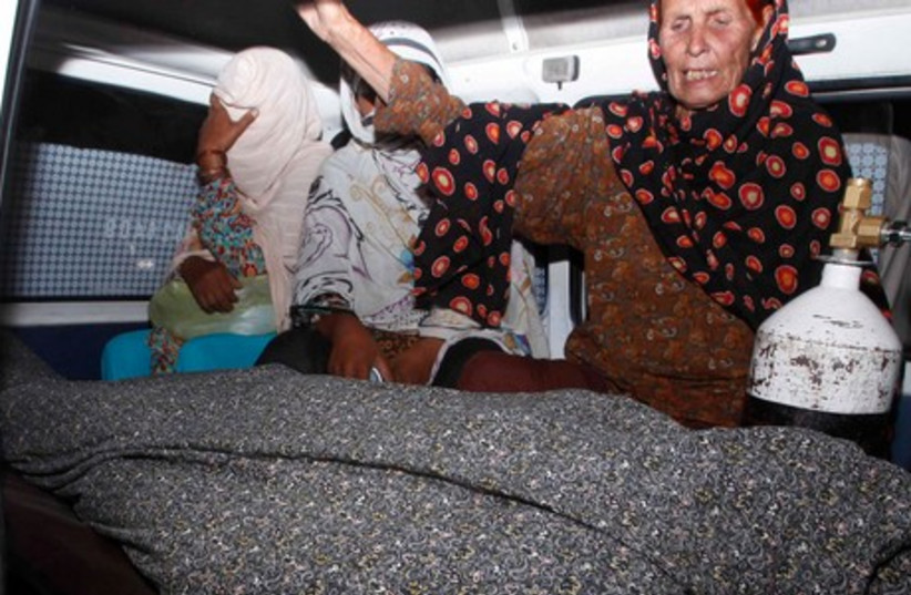 Women mourn over the body of their relative, Farzana Iqbal, who was killed by family members, in an ambulance outside of a morgue in Lahore. (photo credit: REUTERS)