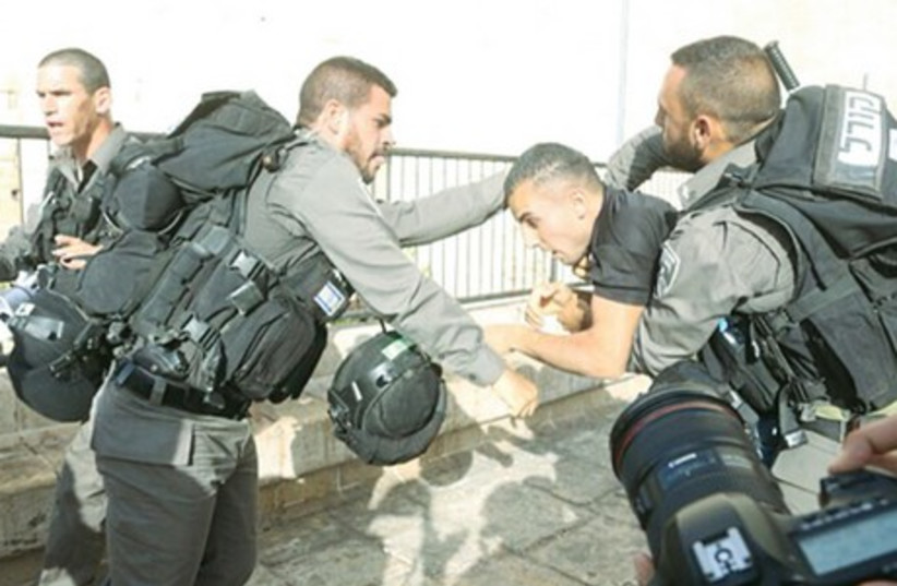 BORDER POLICE detain a Palestinian during clashes at a protest against the Jerusalem Day march, near Damascus Gate in the capital's Old City. Nine Palestinians were detained on suspicion of throwing stones at policemen and march participants (photo credit: MARC ISRAEL SELLEM)