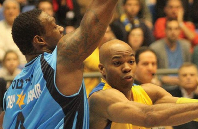 Maccabi Tel Aviv center Alex Tyus (right) has yet to display his best form against Yancy Gates (left) and Hapoel Eilat in the BSL semis, but he is hoping to finally do so in tonight's Game 3 at Nokia Arena, with the best-of-five series tied 1-1 going in. (photo credit: ADI AVISHAI)