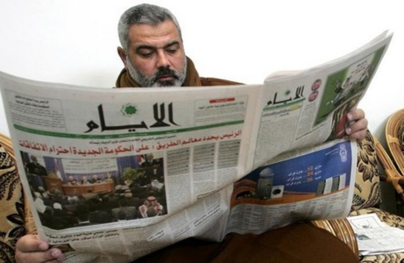 Hamas leader Ismail Haniyeh reads a newspaper. [File] (photo credit: REUTERS)