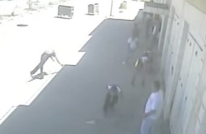 FREEZE FRAME from the surveillance footage: The 'victim' clearly breaks his fall. (photo credit: screenshot)