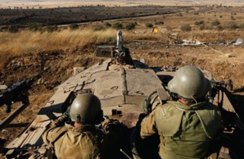 SOLDIERS SIT atop a tank as they watch the border with Syria near Quneitra (photo credit: REUTERS)