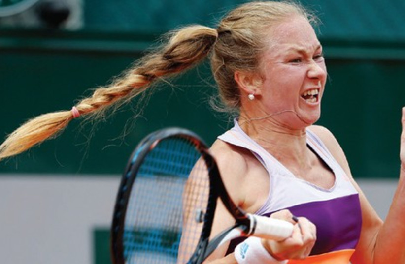 Julia Glushko of Israel returns to Kirsten Flipkens of Belgium during their second-round singles match yesterday at the French Open in Paris. Glushko matched her longest run at a Grand Slam by advancing with a 6-4, 3-6, 6-4 victory. (photo credit: REUTERS)