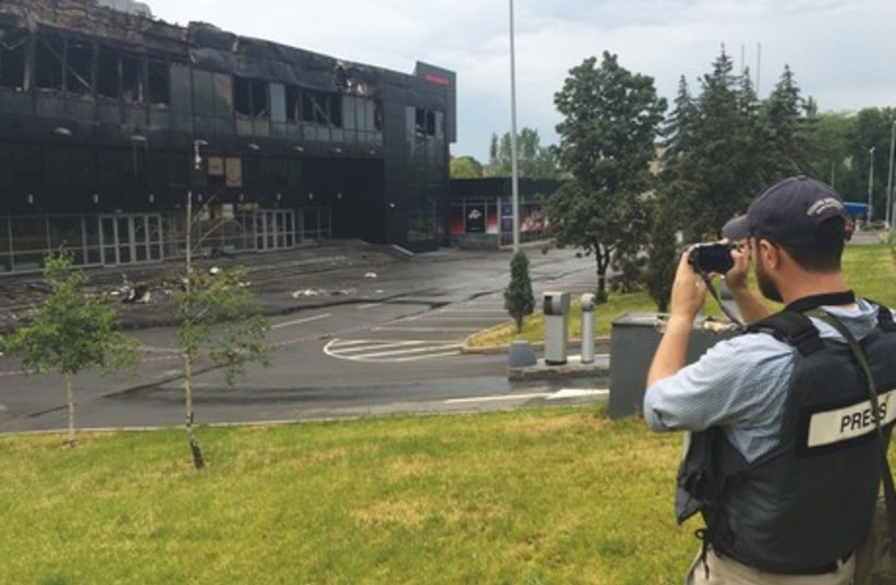'POST' REPORTER Sam Sokol takes a picture of a building damaged in a battle in separatist-controlled Donetsk yesterday. (photo credit: Courtesy)