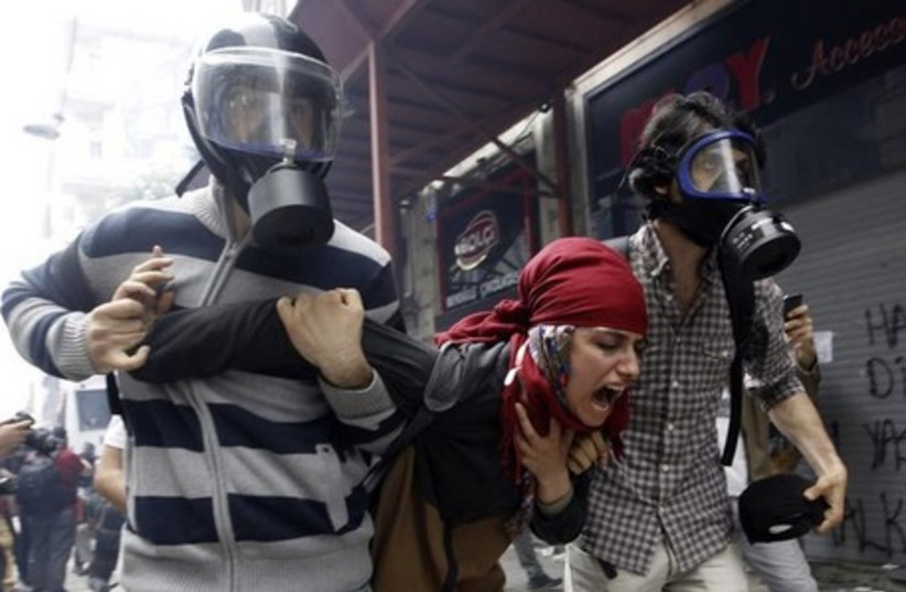 Plain clothes police officers detain a demonstrator during a protest in Istanbul May 31, 2014. (photo credit: REUTERS)