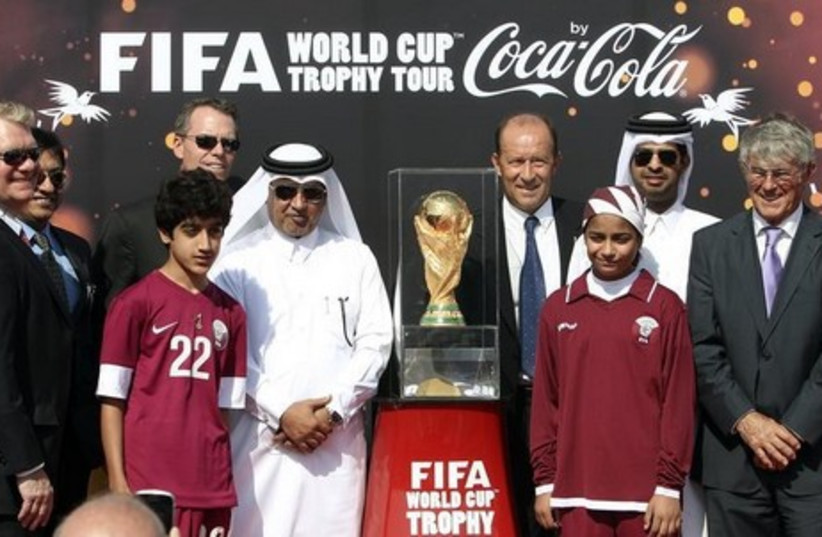 Qatari soccer officials pose with others next to the FIFA World Cup trophy following its arrival in Doha (photo credit: REUTERS)