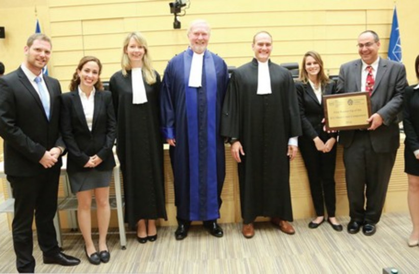 ICC JUDGE Howard Morrison (in blue), coach Dr. Rotem Giladi (holding the award) and the Israeli team pose in The Hague.   (photo credit: ICC)