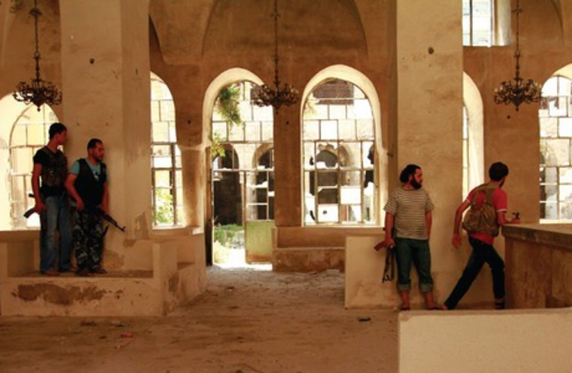 Syrian rebel fighters at a synagogue in Aleppo. (photo credit: REUTERS)