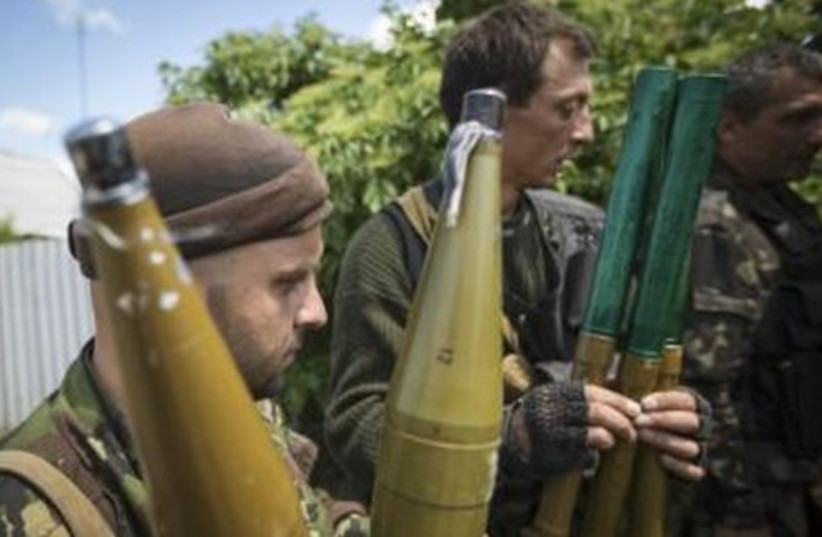Pro-Russian separatists hold rocket-propelled grenade (RPG) projectiles as they get ready to go to the battle line in Seversk (Siversk), located near the town of Krasny Liman, Donetsk region, June 19, 2014 (photo credit: REUTERS)