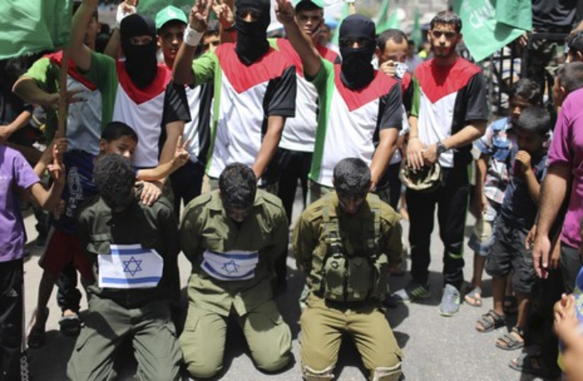 Hamas supporters enact a scene simulating the abduction of three Israeli soldiers during a rally in the Gaza Strip, June 20, 2014.  (photo credit: REUTERS)