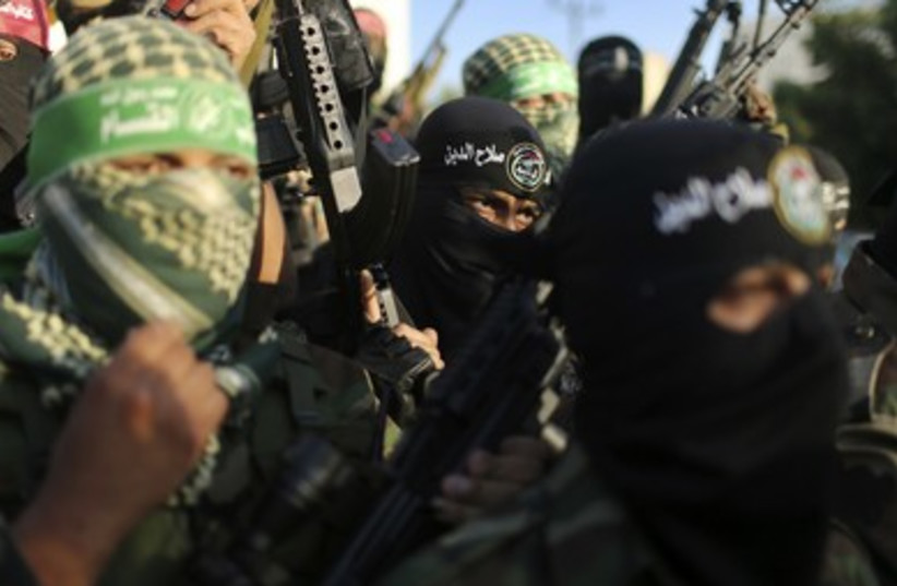 Palestinians militants from various armed factions, including Hamas, attend a news conference in Gaza City. (photo credit: REUTERS)