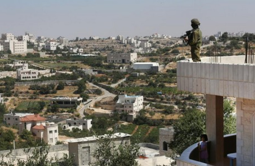 An IDF soldier gazes out over Hebron in search of three missing teens. (photo credit: MARC ISRAEL SELLEM)