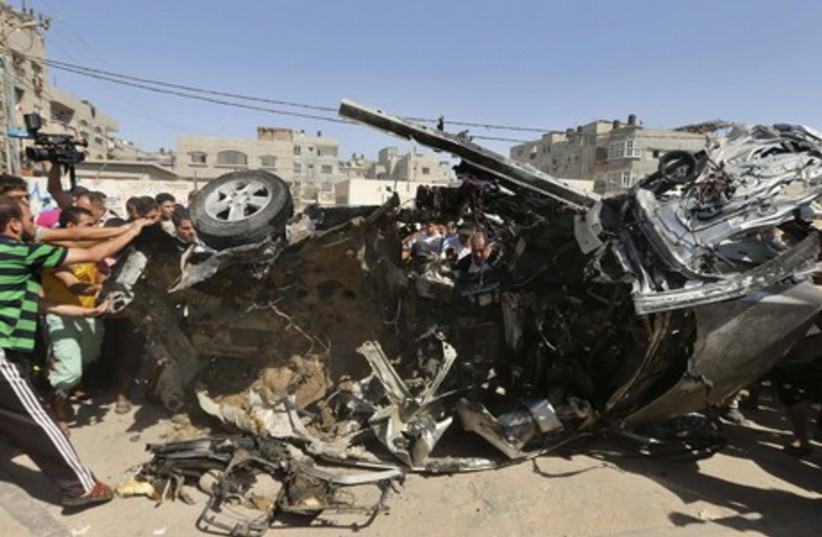 Palestinians survey the wreckage of an IAF strike that killed two terrorists in Gaza. (photo credit: REUTERS)