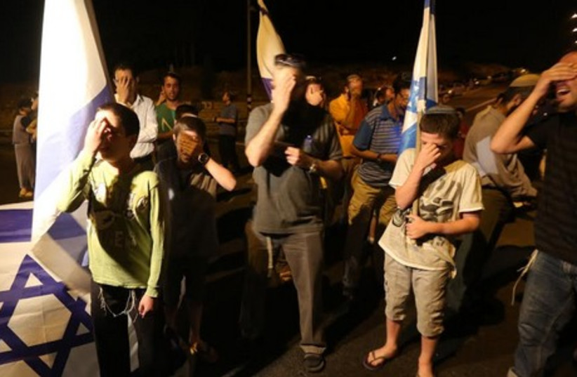 Bystanders mourn the deaths of the three kidnapped boys at Halhul junction (photo credit: MARC ISRAEL SELLEM)
