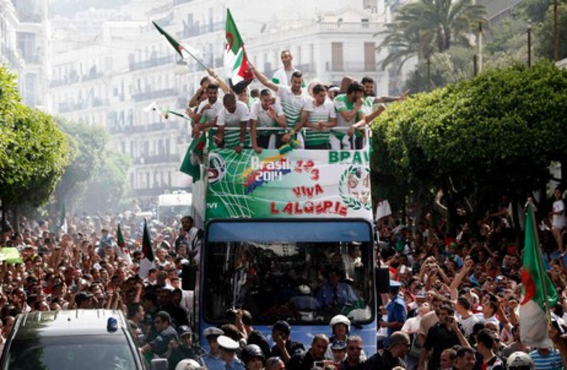 Algeria's soccer players (on bus) are welcomed by fans in downtown Algiers, after returning from the 2014 World Cup soccer tournament, July 2, 2014 (photo credit: REUTERS)