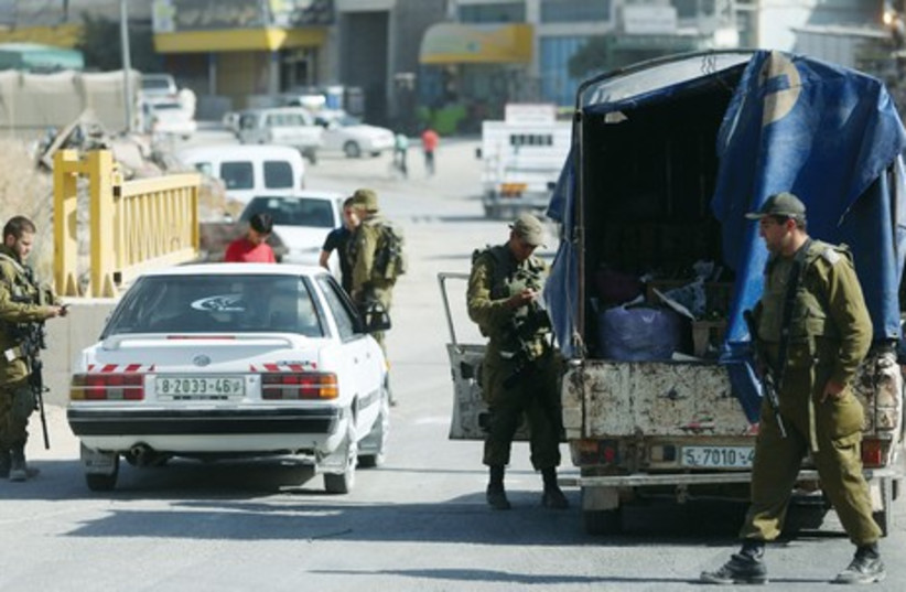 IDF soldiers man a checkpoint in Hebron on June 17 (photo credit: MARC ISRAEL SELLEM/THE JERUSALEM POST)
